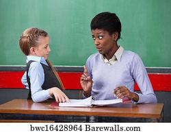 Female Teacher Scolding Schoolgirl At Desk